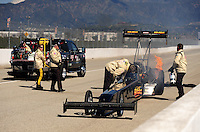 Feb. 27, 2011; Pomona, CA, USA; NHRA top fuel dragster driver Troy Buff is tended to by the safety safari after exploding an engine during the Winternationals at Auto Club Raceway at Pomona. Mandatory Credit: Mark J. Rebilas-