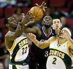 Philadelphia 76ers' Reggie Evans, center, battles for a rebound with Seattle SuperSonics' Jeff Green, left, and Delonte West, right, in a NBA basketball game during the second half Monday, Dec. 31, 2007 in Seattle. The 76ers beat the SuperSonics 98-90.  (AP Photo/Jim Bryant).. .