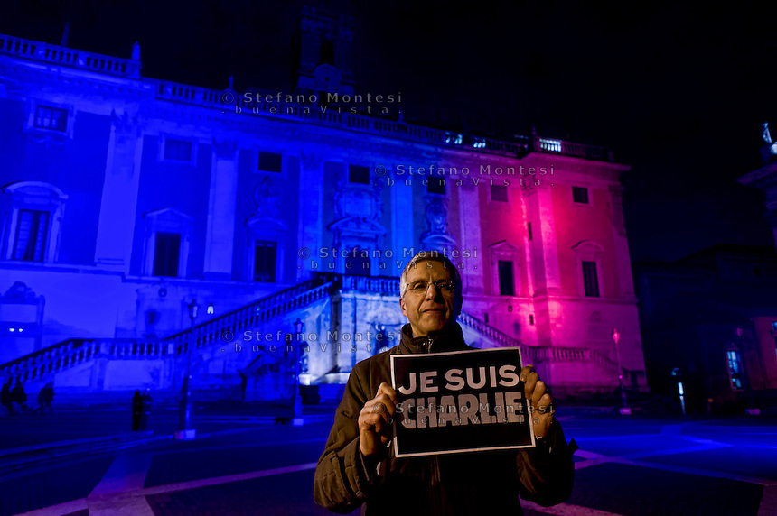 Roma, 8 Gennaio  2015<br /> Il Campidoglio illuminato dai colori blu, bianco e rosso della bandiera francese, in memoria delle 12 persone che ieri hanno perso la vita nell'attentato a Parigi nella  sede del giornale satirico Charlie Hebdo. Nella foto: Luigi Nieri, vice sindaco di Roma con il cartello con scritto Je suis Charlie<br /> Rome, January 8, 2015<br /> The Capitol building lit by the colors blue, white and red of the French flag, in memory of the 12 people that  who lost their lives in the attack yesterday in Paris at the headquarters of the satirical magazine Charlie Hebdo.Pictured: Luigi Nieri, deputy mayor of Rome with a sign: Je suis Charlie