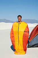 man having fun while standing in a zipped sleeping bag in the desert