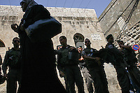 A Palestinian woman passes next to police in the old city of Jerusalem on September 13, 2013. Israeli police declared an age limit on Friday for Palestinians wanting to enter the Old City, only allowing males above the age of 45 and all females to enter, as Yom Kippur, the Jewish day of atonement, begins at sundown. Photo by Oren Nahshon