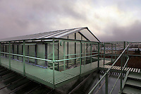 Rooftop of the Tropical Rainforest Glasshouse (formerly Le Jardin d'Hiver or Winter Gardens), 1936, René Berger, Jardin des Plantes, Museum National d'Histoire Naturelle, Paris, France. View from the side of walkways and highest roof structure of the glass and metal Art Deco building beneath a cloudy sky.