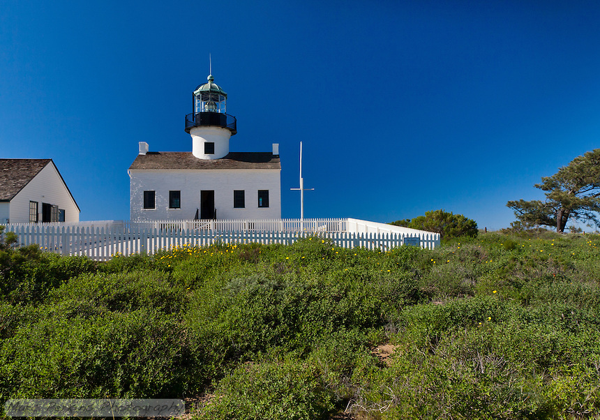 A wide-angle view of Old Point Loma Light as seen from the east on a crystal clear blue sky winter's day.  The foreground bushes mostly block the concrete water catchment basin.  The lighthouse itself is clearly visible, as is the assistant keeper's house (to the left).  Note: Please contact me if you're interested in purchasing this image for use printed or displayed large, as I should give you some background on the image (the sky has been burned to reduce uneven polarization, and it should be test-printed before final images are made).