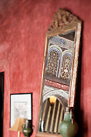 Glimpses of the decorated wall above the archway reflected in the mirror of the Red Apartment at the Riad Dar Darma