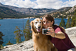 A woman takes a self portrait with her golden retriever at Lower Echo Lake, El Dorado National Forest, California