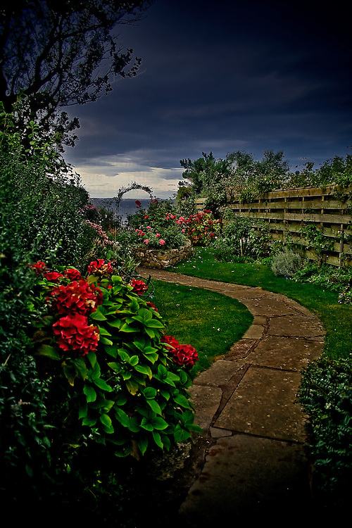A garden path with stormclouds overhead.