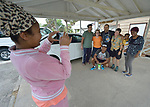 Kisanet Araya, an asylum seeker from Eritrea, takes a photo of other immigrants and volunteers at the Posada Providencia, a shelter in San Benito, Texas. Sponsored by the Catholic Sisters of Divine Providence, the shelter provides a safe place for people in crisis from all over the world who are seeking legal refuge in the United States.
