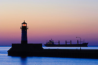 A ship awaits entry to Duluth Harbor with the north breakwater light silhouetted against the glow of the sunrise.
