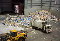 New York Dept. of Sanitation trucks deliver mountains of trash from the city's curbside recycling program to the Sims Municipal Recycling facility in Sunset Park in Brooklyn in New York on Tuesday, September 30, 2014. Opened in 2013 the state-of-the-art facility processes the majority of the city's commingled curbside recyclables. (© Richard B. Levine)