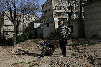 "A Free Syria Army sniper looks through the scope of his rifle to review any possible regime sniper activity that may pose a threat to their position at a children's park in Aleppo. ..Cobbler's Park, an open space in the Bustan Al-Qasr neighborhood of Aleppo under Free Syria Army control, has been renamed ""Martyr's Park"", since the revolution arrived in Aleppo in July of 2012.  A patch of dirt that lies next to children's swings, slides and monkey bars now serves as this neighborhood's makeshift cemetery. On January 29, 2011, 110 bodies floated down a water canal (which is part of the river Qweiq) that separates this rebel-controlled area from the regime side on the opposite side of the canal. Many of the showed signs of torture and most where executed with their hands bound behind their backs. In the weeks after this incident, dozens more bodies have been discovered in the canal - many of the victims that have not been claimed by family members have been buried here."