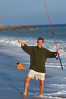 Man surf fishing with a work boot on his line at the beach in Santa Monica, CA