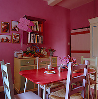 In the bright pink kitchen stands a 1950s pink formica table surrounded by painted wooden chairs and a sideboard