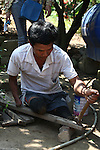 A man who lost both legs and part of his right arm to a land mine salvages nails from a scrap piece of wood in Quang Tri province, Vietnam. According to experts, Quang Tri was the most heavily bombed province of the Vietnam War.  More than 1.3 million unexploded bombs and land mines have been found in Quang Tri since the war ended in 1975.  Project RENEW, along with several other groups, are working to make the province safe within the next five years. April 23, 2013.
