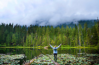 Photojournalist Julie Busch Branaman takes in the scenery at Elk Lake after climbing up to the Blue Glacier on Mt. Olympus. The Hoh River trail in Olympic National Park starts in the mossy and lush Hoh Rain Forest. From there you climb over 5,000 ft. in elevation along towering trees and rock to overlook the windswept Blue Glacier on Mt. Olympus. Tracing your steps back to the Hoh River visitors center the hike covers over 36 miles of diverse climate and ecosystems ranging from temperate rain forest to alpine.