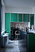 The contemporary kitchen is fitted with a wall of units with green polished glass doors