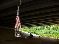 The American flag hangs among a homeless person's camp beneath a Houston, Texas overpass in 2005.