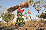 Her daughter Joyce on her back, Jenifa Tiyu carries home thatch she has cut in the Southern Sudan village of Yondoru. Families here are rebuilding their lives after returning from refuge in Uganda in 2006 following the 2005 Comprehensive Peace Agreement between the north and south. A United Methodist, she will use the thatch for roofing. NOTE: In July 2011, Southern Sudan became the independent country of South Sudan