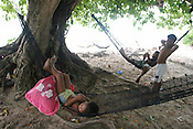 Children relaxing on the beach on the island of Kiribati in the South Pacific. The islands, and their way of life, is endangered by rising sea water levels which are eroding the fragile atoll, home to approximately 92,000 people.