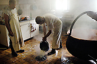 Pouring water from a bucket into the drain in the kitchen. Making Zigger (a form of curd cheese) from the remaining whey...Cowherd and cheesemaker spends 100 days in the summer, high up in the mountains, tending cows and pigs and making cheese at Balisalp and Käserstatt near Meiringen, Switzerland.
