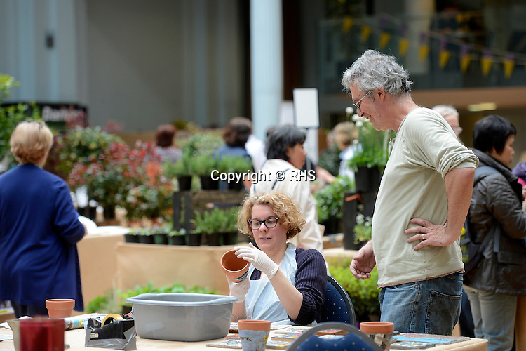 A visitor tries mosaic making at an RHS Secret Garden Sunday.