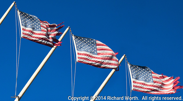 In a composite of three images, a tattered and frayed US flag waves in the wind over the Spinnaker Yacht Club, San Leandro, California.