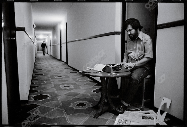 A reporter at the Intercontinental Hotel works by emergency light in the hallway during a power outage. Tehran, January 15, 1979
