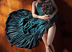 Sensual artistic abstract portrait of a woman in a bohemian blue dress with bare legs lying on the floor with a bouquet of wild flowers
