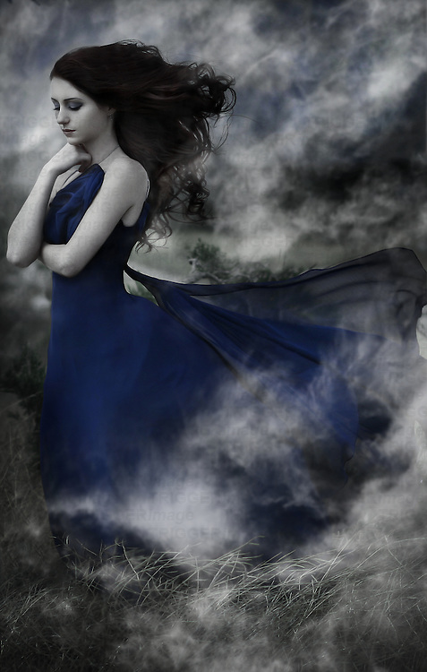 Young female with long black hair blowing in the wind wearing a blue dress standing outdoors with smoke effect