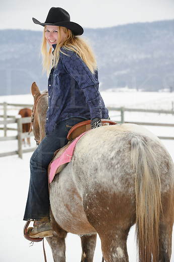 Pretty blonde woman riding her Appaloosa horse, twenty-something in casual western wear with black cowboy hat, rear view looking over shoulder, winter outdoors in snow, Pennsylvania, PA, USA.