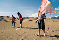 Hannah Emery, 7, holds onto her kite as mom Theresa, center, and brother Kyle, 10, make adjustments to another kite at the Great Sand Dunes National Park and Preserve in souuthern Colorado, Friday, April 27, 2007. The Emerys, of the Denver suburb of Arvada, had planned to travel to the beaches of Texas for kite flying, but opted for the 40-square-mile dune field of the park instead. (Kevin Moloney for the New York Times)<br /> <br /> jason.emery@exceldriverservices.com<br /> 303-906-1906 Jason cell<br /> 303-883-5052 Theresa cell