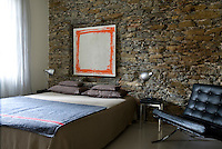 This simply furnished bedroom features a natural stone wall