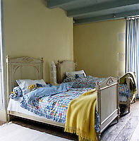 This children's bedroom is unashamedly nostalgic with antique bedsteads, patchwork-style duvet covers and ribbon-edged cushions