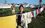 A woman hangs laundry while her husband holds their two-month old child outside a tent where they live in Tacloban, a city in the Philippines province of Leyte that was hit hard by Typhoon Haiyan in November 2013. The storm was known locally as Yolanda. The ACT Alliance has been active here and in affected communities throughout the region helping survivors to rebuild their homes and recover their livelihoods.