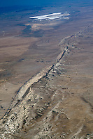 Aerial view of the San Andreas Fault in the Carrizo Plain. The San Andreas Fault is a continental transform fault that runs a length of roughly 800 miles (1,300 km) through California in the United States. The fault's motion is right-lateral strike-slip (horizontal motion). It forms the tectonic boundary between the Pacific Plate and the North American Plate (wiki 2009)