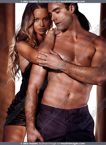 Artistic sensual portrait of a sexy young couple, a woman with long blond hair in a night shirt and a man with bare torso