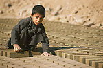 Afghan refugee children work long hours to help their families survive. Near Shamshatoo camp, this boy works in a brickyard..