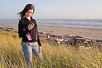 Young adult woman standing and texting on hillside above beach Westport Washington State USA