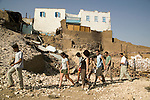 25-year-old Belgian egyptologist, Pierre Coussement, who has been visiting the village for eight years, leads a group of enthusiasts. On their way up to see the tombs at the Valley of the Nobles, they walk pass the debris of demolished houses, much to their regret as for them visitng the old village was an integral part of the experience of visiting Qurna..Luxor, Egypt..Photo: Eduardo Martino