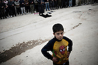 SYRIA - Al Qsair. A child stands in a pray for the three men kidnapped and tortured by shabiha (militias of the regime) during three days. The bodies were found  in a main street of Al  Qsair, on February 14, 2012. ALESSIO ROMENZI