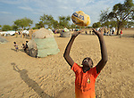 A boy plays with a deflated soccer ball in an internally displaced persons camp in Aweng, South Sudan. Families started arriving here shortly after fighting broke out in December 2013, and new families continued to arrive in March 2014 as fighting continued. The ACT Alliance is providing the displaced families and the host communities affected by their presence with a variety of support.