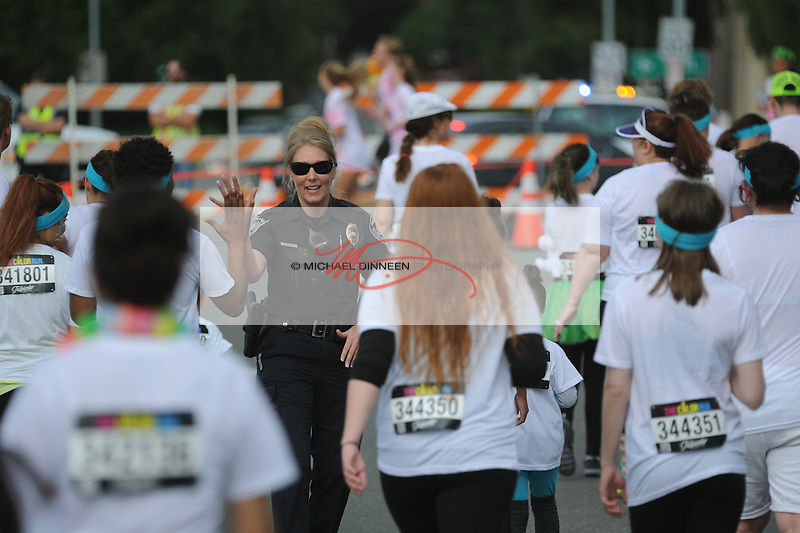 APD Officer Kemberly Semeniuk  greets participants as they begin the Color Run.  Photo for the Star by Michael Dinneen