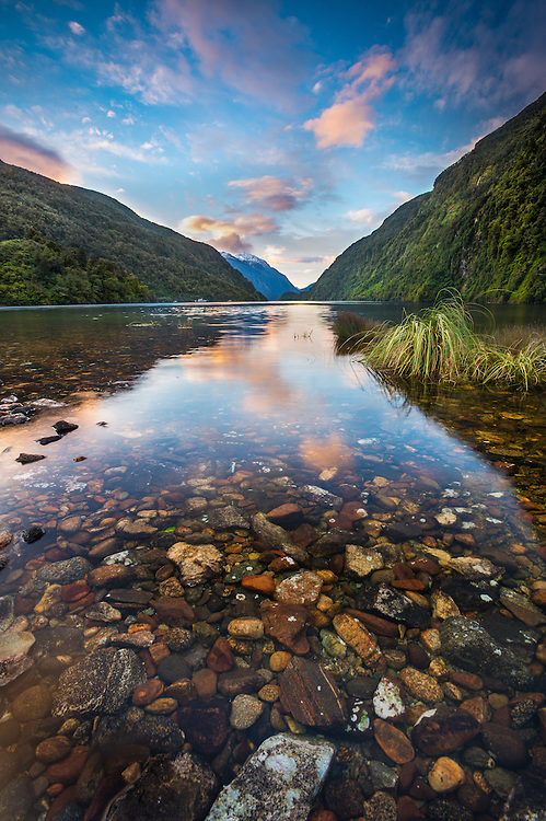 Soft pink clouds are reflected in calm waters at Doubtful Sound, Fiordland National Park, Southland, New Zealand