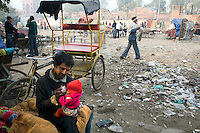 A homeless rickshaw wallah gives his baby child a drink of tea at dawn in Urdu Park, a notorious area for the destitute and drug addicts near the Jama Masjid.