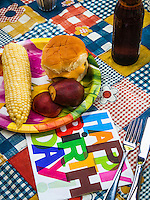 A 4th of July barbecue with corn on the cob, a burger, fruit, a beer and napkin with fork and knife.