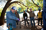 To prepare a tree for phosphate injections, small holes must be drilled into tree.  Schmidt uses a cordless drill to demonstrate the correct angle on a piece of wood.