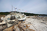 The hull of a shattered fishing boat lies atop a mountain of crushed oyster shells after being hauled out of  waters at Konabekura, Oshika Peninsula, Miyagi Prefecture, Japan on 26 May, 2011..Photographer: Robert Gilhooly