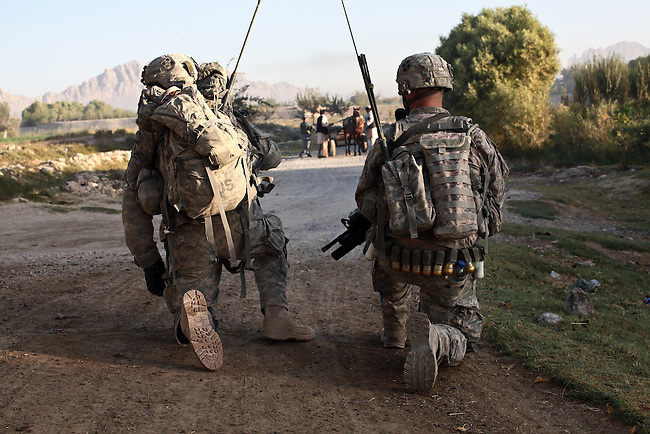 Two U.S. radio operators from Company D, 1st Battalion, 22nd Infantry kneel on a dirt road while Afghan police search local villagers for weapons during an early morning patrol in Malajat, near Kandahar, Afghanistan.  Oct. 4, 2010. DREW BROWN/STARS AND STRIPES