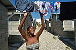 """Asline ALbert hangs clothes to dry in a model resettlement village constructed by the Lutheran World Federation in Gressier, Haiti. The settlement houses 150 families who were left homeless by the 2010 earthquake, and represents an intentional effort to """"build back better,"""" creating a sustainable and democratic community."""