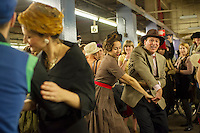 New Yorkers, tourists and subway buffs, some in period garb, dance on the platform at the Second Avenue Subway stop before traveling on a vintage MTA Nostalgia Train Christmas season ride on Sunday, December 16, 2012. The straps, ceiling fans and rattan seats are a far cry from the plastic and air conditioning in modern subway cars. The Metropolitan Transit Authority has several of these trains for the various subway lines which they put into use for special occasions. The trains normally reside in the New York City Transit Museum in downtown Brooklyn where they can be visited every day.  © Frances M. Roberts)