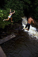 Kids jumping off very high bridge into pond on Hamakua Coast near Hilo, Hawaii.